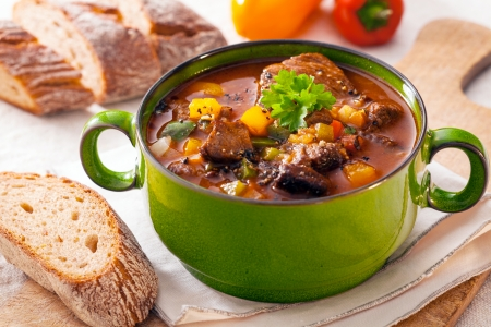 pot: Delicious goulash casserole in a metal pot with thick rich gravy, meat and vegetables for a wholesome meal Stock Photo