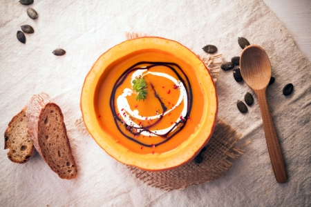 vegetable soup: Overhead view of colourful orange autumnal pumpkin soup served in the rind of the gourd and garnished with cream Stock Photo