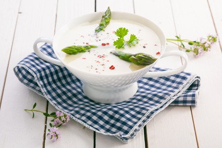 potage: Cream of asparagus soup with fresh green asparagus tips and seasoned with spices served in a bowl on a blue and white checked cloth