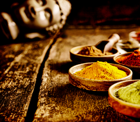 curry powder: Low angle view of a rustic dish of Asian curry powder on a grunge wooden surface with copyspace