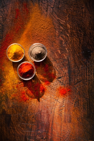 Cooking using fresh ground spices with three small bowls of spice on a wooden table with powder spillage on its surface, overhead view with copyspace Stock Photo - 22230437