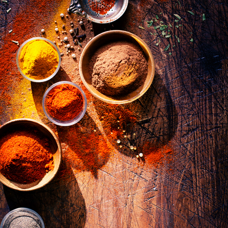 Overhead view depicting cooking with spices in a rustic kitchen with bowls of colourful ground spice and scattered powder on an old scored wooden counter with copyspace Stock Photo - 22230440