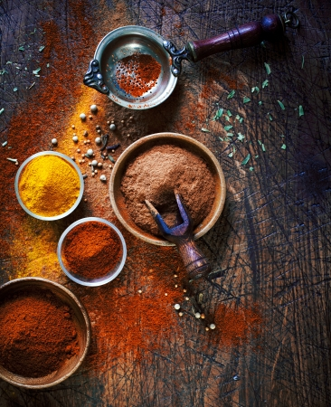 country kitchen: Overhead view of colourful dried ground spices in bowls spilling onto an old aged scored wooden surface in a country kitchen with a vintage sieve or strainer Stock Photo
