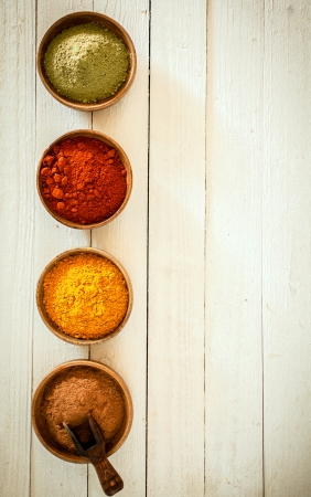 Border of colourful spices arranged in a vertical row with chilli, curry, red pepper and matcha powder in small bowls on a background of white painted boards with copyspace Stock Photo - 22230442