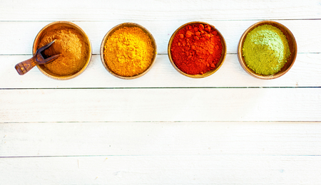 Overhead view of a line of four colourful ground spices in wooden bowls on white painted boards with copyspace below Stock Photo - 22230245