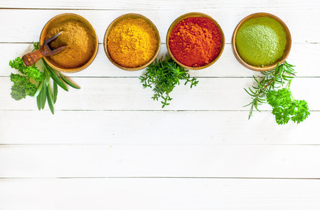 Colourful culinary herbs and spices in wooden bowls standing in a row on white painted boards with copyspace below, overhead view Stock Photo - 22230251