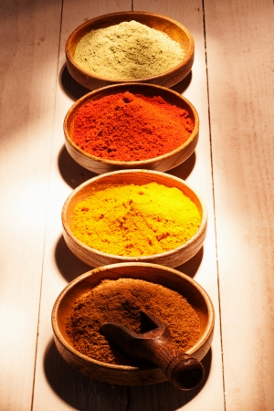 Line of colourful ground spice with four bowls of chilli powder,red cayenne pepper, curry and ground green tea on wooden boards Stock Photo - 22230255