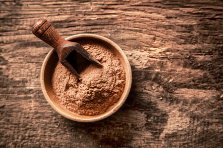 Overhead view of a bowl of finely ground cinnamon powder made from the bark of a tree and used as a seasoning in both savoury and sweet cooking recipes Stock Photo - 22230265