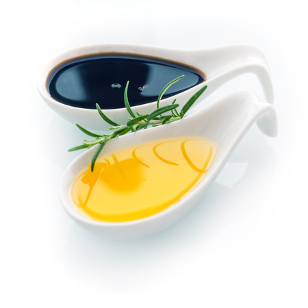 Sprig of fresh rosemary for seasoning food with golden virgin olive oil in a ceramic spoon on a white background for healthy cooking and cuisine photo