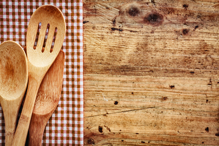 Wood background with copyspace bordered by a red and white country cloth with wooden kitchen utensils lying on top of it photo