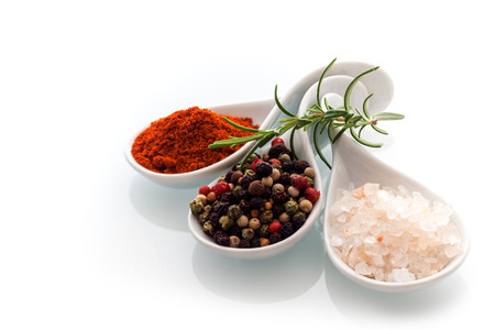 spice: Himalayan rock salt, red cayenne pepper and black peppercorns in ceramic spoons with a sprig of fresh rosemary for seasoning and flavouring food