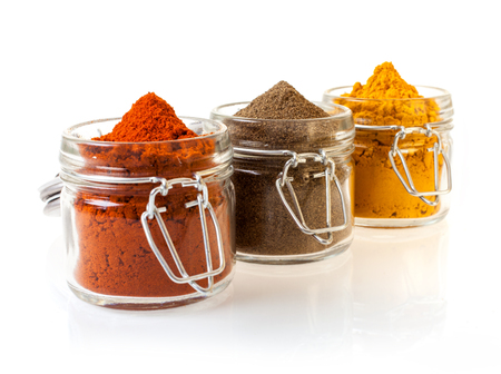 Three glass jars filled with colourful ground spices including chilli, curry and cinnamon, on a white background
