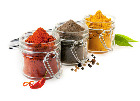 Three glass containers filled with ground culinary spices with chilli peppers, black peppercorns and curry powder on a white background