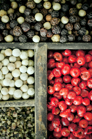 pink brown: Different varieties of peppercorns with whole dried black, white and pink peppercorns with their colourful red colour used as a spice and condiment