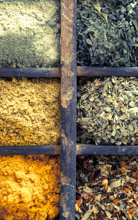 flavouring: Close up overhead view of assorted dried herbs and spices in an old vintage wooden printers tray for use as seasoning and flavouring in cooking Stock Photo