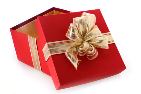 open gift box with tilted lid and decorative gold ribbon and bow for celebrating christmas