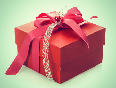 Red gift box tied with a decorative bow for celebrating Christmas, Valentines, birthday or an anniversary on a pale green background Stock Photo - 22727484