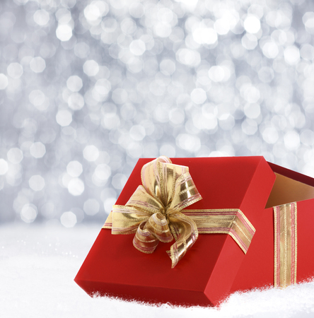 x mas parties: Colourful red Christmas gift decorated with a gold ribbon and bow in winter snow with a bokeh of falling snowflakes and copyspace for your seasonal greeting