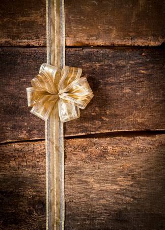 christamas: Pretty ornamental gold bow and ribbon over dark textured wooden planks with copyspace for your text or Christmas, anniversary or birthday greeting Stock Photo