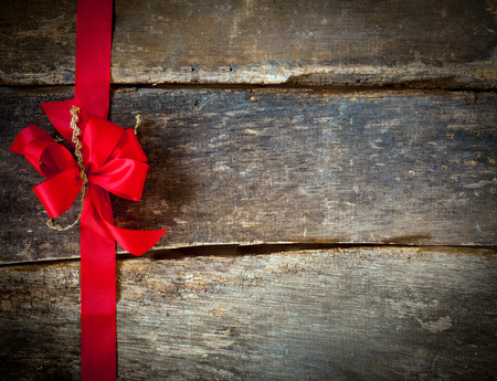 Festive red bow and ribbon forming a border for a Christmas card over rustic wooden planks with copyspace for your greeting or wishes photo