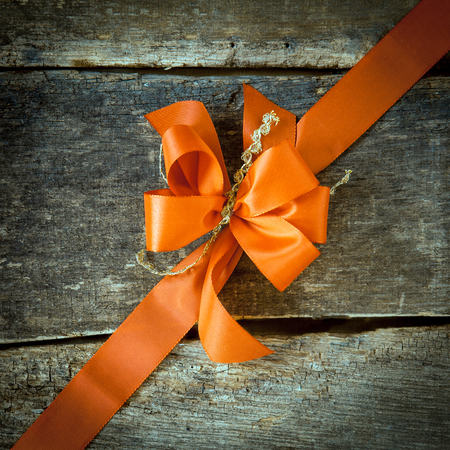 christmass: Ornamental diagonal orange ribbon and decorative bow on rustic dark textured wood with copyspace for your greeting or Christmas wishes Stock Photo