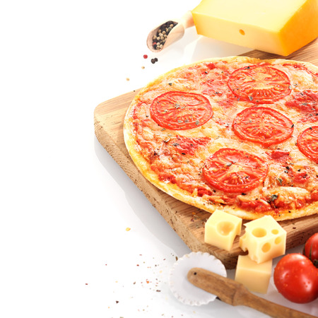 Home baked cheese and tomato pizza surrounded by fresh ingredients and a pizza wheel and served on a wooden board over white photo