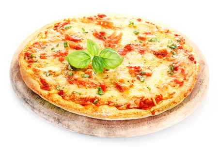 Pizza Margherita isolated on white backgroundPizza Margherita placed over a pizza board decorated with basil leafs isolated on white background photo