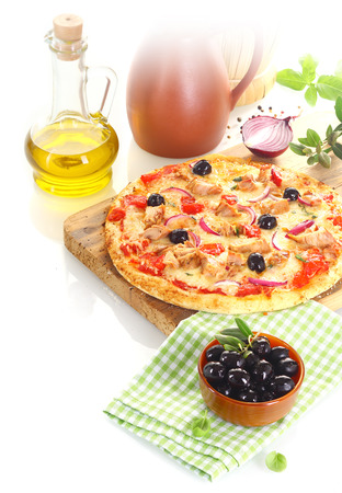 Pizza made of tuna, olives, onion and basil over a wooden board surrounded by the composing ingredients photo