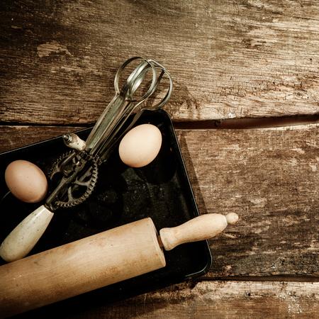 batidora: Concepto de hornear con un rodillo de madera y viejos batidor de huevos que descansa sobre una bandeja para hornear con dos huevos frescos en la antigua tablas de madera