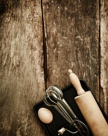 batidora: Hornear en una cocina rústica con una vista aérea de una vieja batidora manual y un rodillo tirado en una bandeja de horno con un huevo fresco sobre una superficie de madera con copyspace Foto de archivo