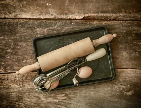 batidora: Rústicos utensilios para hornear con un viejo rodillo de madera y el batidor de huevos manual de mentir sobre una bandeja para hornear de metal con un huevo fresco en una vieja mesa de madera con textura manchada