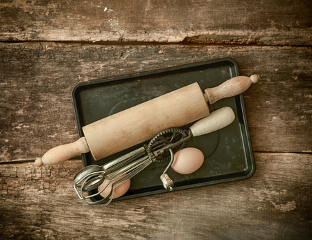 Rustic baking utensils with an old wooden rolling pin and manual egg beater lying on a metal baking tray with a fresh egg on an old stained wooden textured table photo