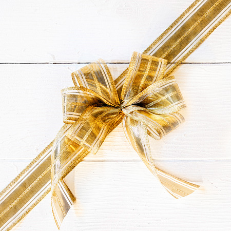x mass: Pretty ornamental golden Christmas bow and ribbon laid diagonally across a background of white painted wooden boards with copyspace for your seasonal message Stock Photo