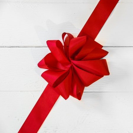 Romantic vivid red Christmas or Valentines bow placed diagonally across white painted boards as a festive background for your greeting or wishes Stock Photo