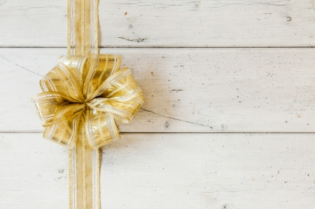 x mass: Metallic gold decorative Christmas bow forming a border on the left on a background of rustic white painted wooden planks with copyspace for your seasonal greeting