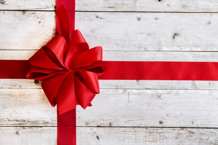 christmas bow: Colourful red Christmas ribbon tied with an ornamental bow on weathered white painted wood with copyspace for your seasonal greeting Stock Photo
