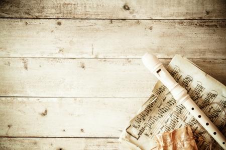 grabadora: Villancicos o el concepto de la m�sica con una grabadora acostado en una p�gina de hoja de m�sica antigua en un rinc�n de un fondo de viejos resistido tablones de madera con copyspace para su mensaje de temporada