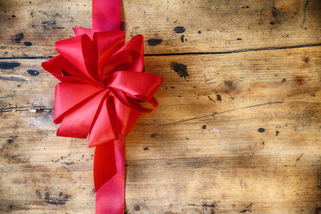 Decorative red ribbon and bow on a rustic wood background with copyspace to celebrate a Merry Christmas, romantic Valentines Day or birthday with a greeting card photo