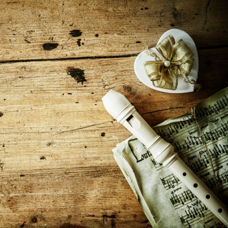 Conceptual image of Christmas night music with a recorder of flute lying on an old music score alongside a decorative heart shaped gift with an ornamental bow, copyspace on the rustic wood background