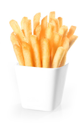 Crisp deep-fried golden potato chips, or French fries, standing upright in a plain white ceramic container over a white background Imagens