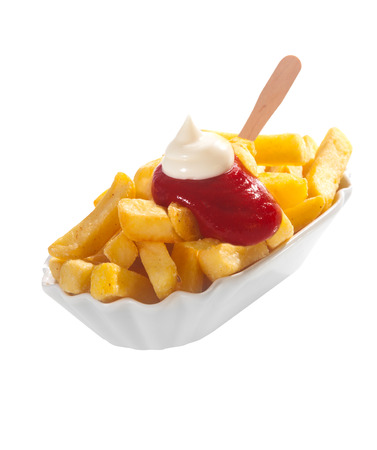 Dish of crisp golden potato chips or French fries topped with ketchup and mayonnaise and served with a wooden spatula over white