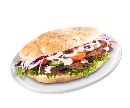 Freshly prepared healthy doner or kebab with mixed salad ingredients and meat in a soft bun served on a plate for a quick meal or snack over a white background Stock Photo