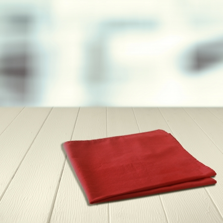 Red napkin on an empty wooden counter against a high key background with copyspace for your product placement or advertisement photo