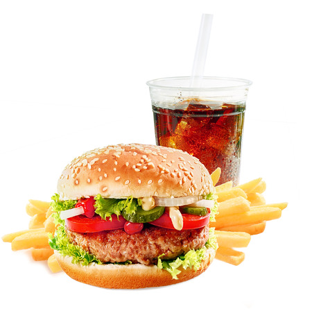 Hamburger on a asesame bun with iced soda drink and crisp golden potato French fries on a white background photo