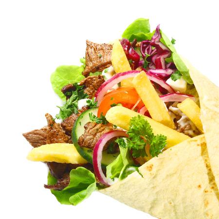 pinchos morunos: Tortilla, Lahmacun o tacos de maíz rellena con carne a la parrilla, papas fritas y ensalada mixta, vista de cerca aislados en blanco