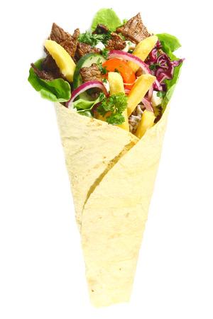 comida arabe: Primer plano de la comida rápida árabe con carne, ensalada verde, cebolla roja, pepino y papas fritas, todo envuelto en un pan de pita