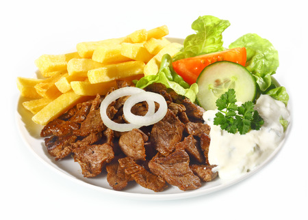 chips: Grilled lean beef nuggets called Doenerteller served with oven-baked potato chips and fresh healthy salads on a white plated for a delicious meal
