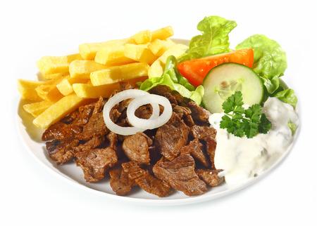 pinchos morunos: Grilled pepitas de carne magra llamado Doenerteller servido con papas fritas al horno y ensaladas saludables frescas en un blanco plateado para una deliciosa comida