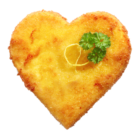 schnitzel: Close-up of tasty fried Schnitzel in heart shape, decorated with parsley leaves, isolated on white background