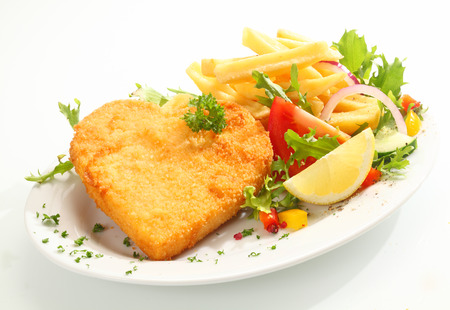 Delicious golden heart shape veal escalope covered in fried breadcrumbs and served with a healthy fresh mixed salad and crisp French fried potato chips Stock Photo